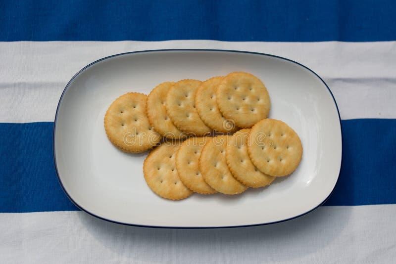 Crackers op witte plaat stock foto's
