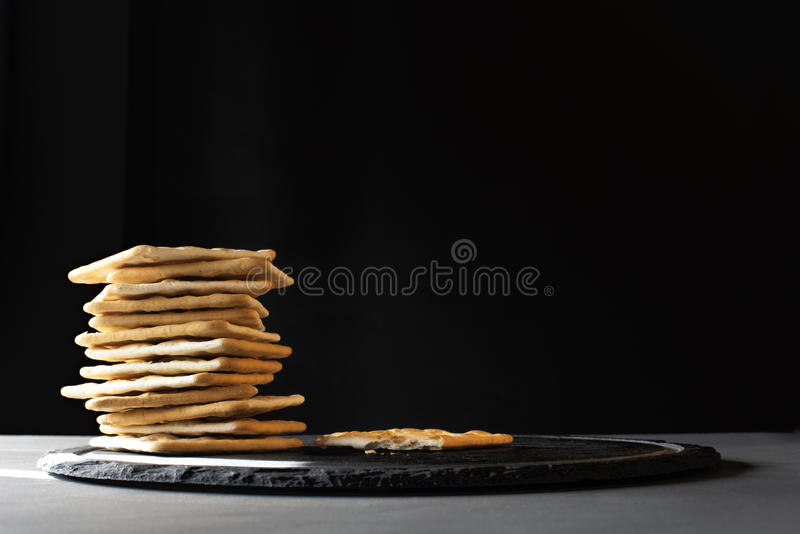 Crackers on a plate. A stack of crackers on a grey slate with dark background royalty free stock image