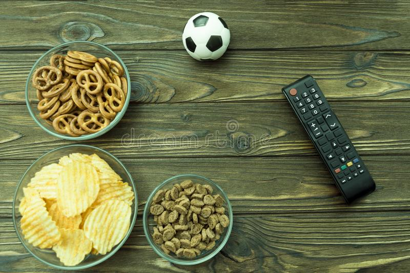 Crackers, potato chips to beer, remote from the TV, soccer ball stock image