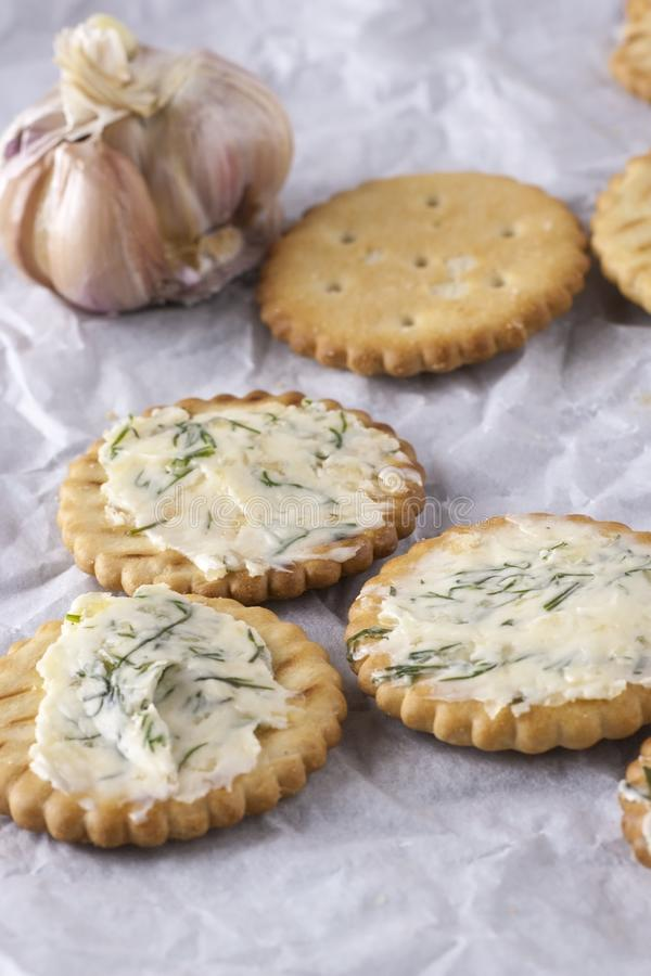 Crackers with smeared garlic butter with dill on white paper stock image
