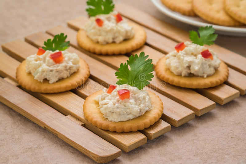 Crackers with tuna salad on wooden plate royalty free stock photos