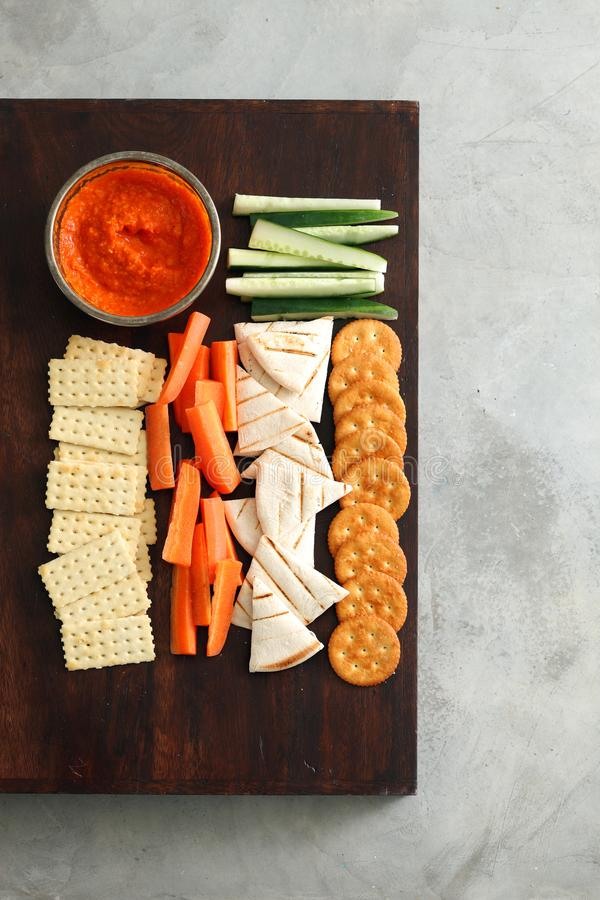 Crackers and vegetables. On wooden board with dipping sauce stock photography