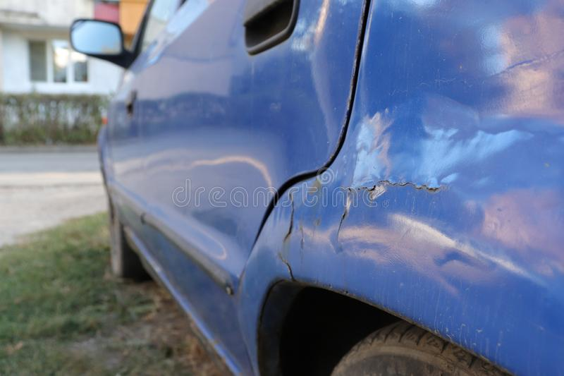 Cracking paint and rust on blue car on the fender, in need of repair royalty free stock image