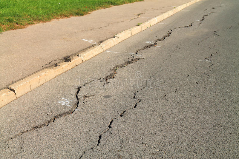Cracks in the asphalt pavement closeup stock photos