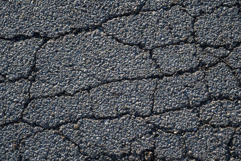 Cracks in asphalt on a street. Image of cracks running through aged asphalt on a street stock image