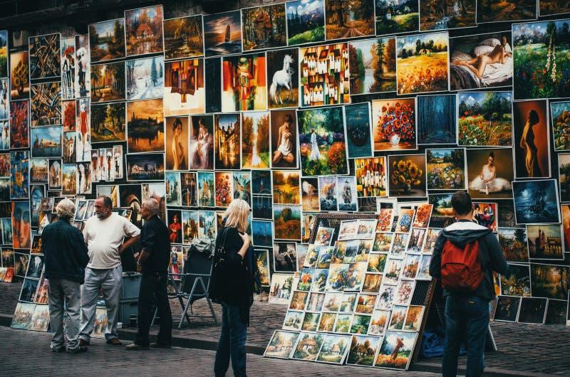 CRACOVIA, POLONIA - 27 GIUGNO 2015: Le pitture da vendere appendono su una parete a Cracovia immagini stock