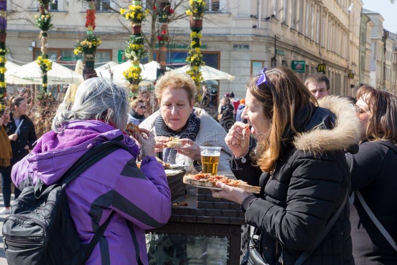 CRACOVIA, POLONIA, il 2 aprile 2018, tre donne anziane mangia l'alimento a della via fotografia stock libera da diritti