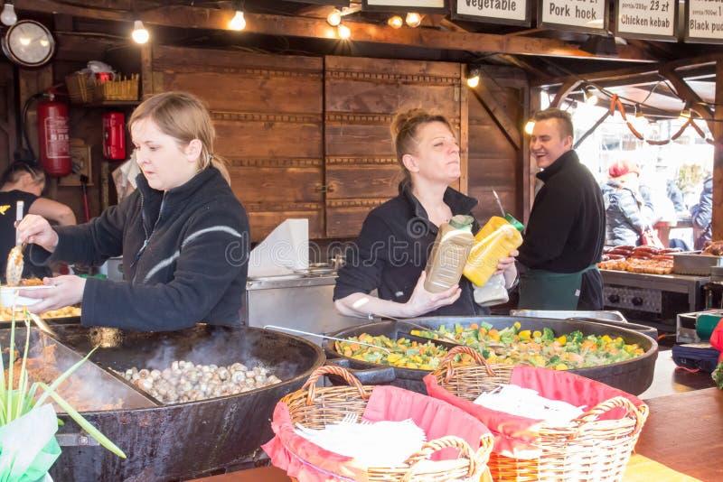CRACOVIA, POLONIA, il 2 aprile 2018, il venditore tiene i grandi barattoli del sa immagini stock libere da diritti