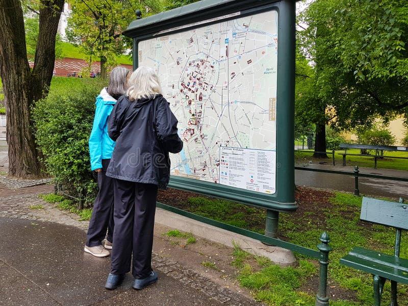 Cracovie, Pologne - 5 9 2019 : Deux touristes de femmes plus âgées regardent une carte de la ville Recherche d'un itinéraire au c images libres de droits