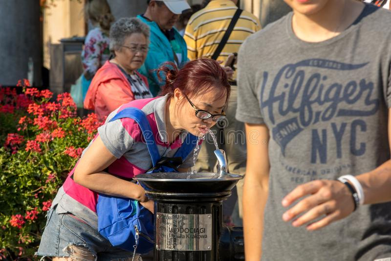 Woman is refreshing at fountain in sweltering hot days on Main Square in Cracow. Cracow, Poland - July 5, 2018: Woman is refreshing at fountain in sweltering hot stock photos