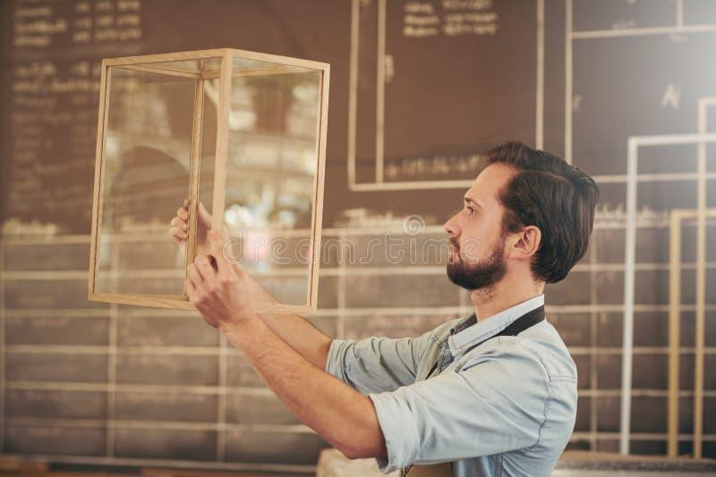 Crafstmanondernemer die een nieuw hout en glasontwerp inspecteren royalty-vrije stock afbeeldingen