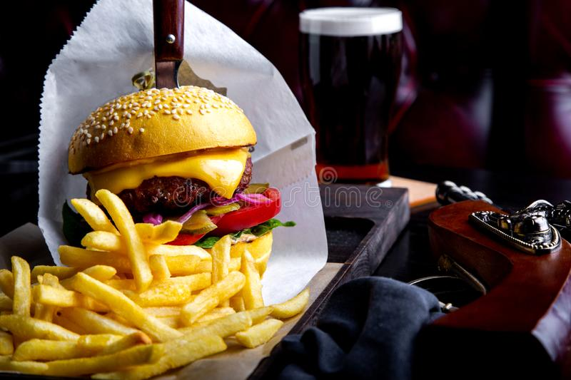 Craft beef burger and french fries on table in restaurant with glass of beer on dark background. Modern fast food lunch. Frame stock images