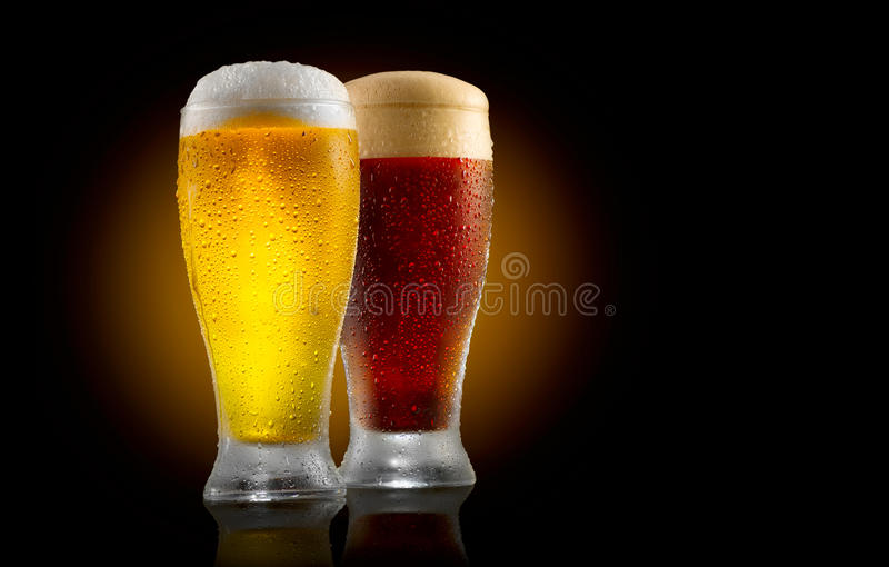 Craft beer. Two glasses of cold light and dark beer isolated on black stock photography
