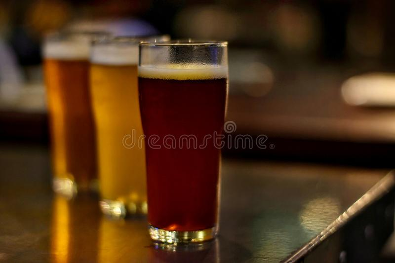 Craft beer on wooden table with blurred background in night club stock images