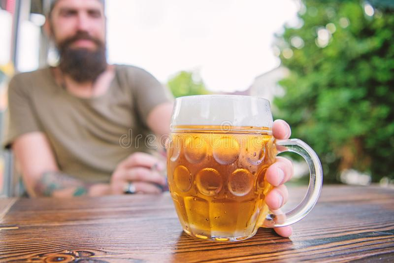 Craft beer is young, urban and fashionable. Distinct beer culture. Mug cold fresh beer on table close up. Man sit cafe. Terrace enjoying beer defocused. Alcohol stock images