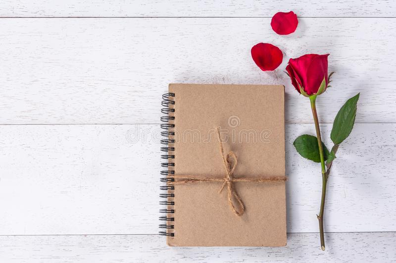 Craft book and red rose. Craft book tied with hemp rope decorated with red rose and petals on white wooden table royalty free stock photo
