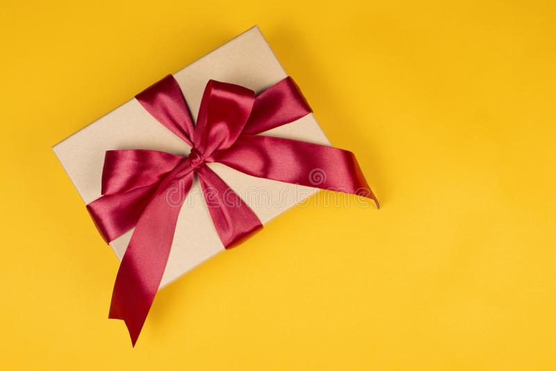 Craft box with big red bow on yellow background. Craft gift box with big red bow tied with ribbon on yellow background stock photo