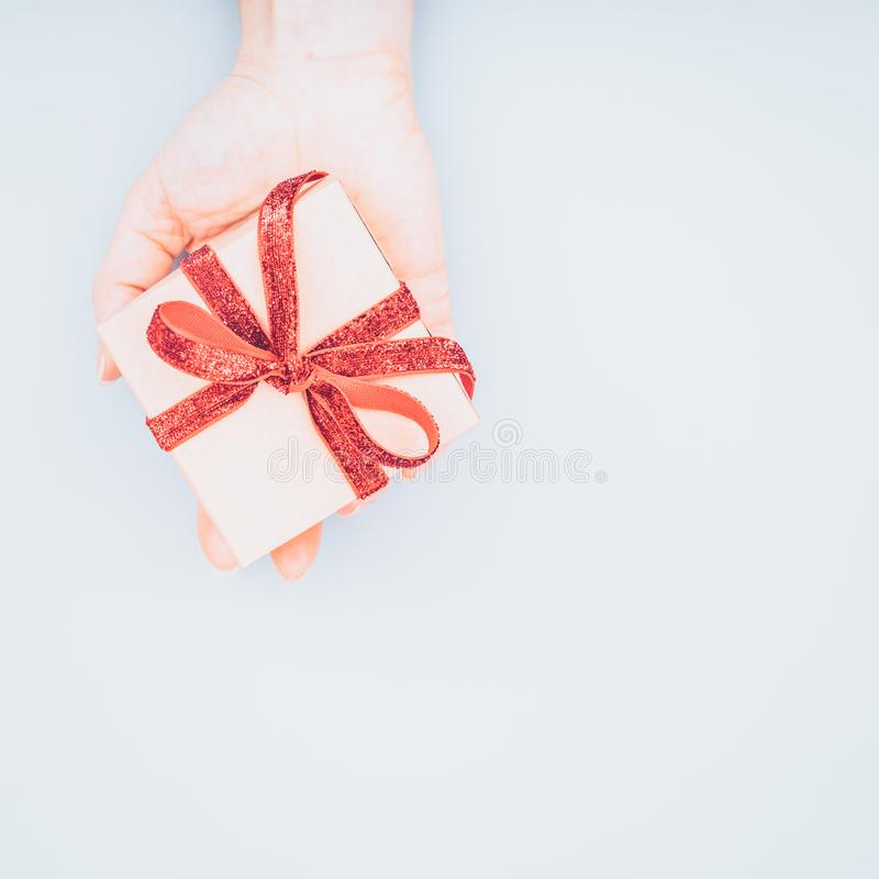 Craft box with red ribbon bow in female hand. Valentine day concept. Trendy minimalistic flat lay design background stock image