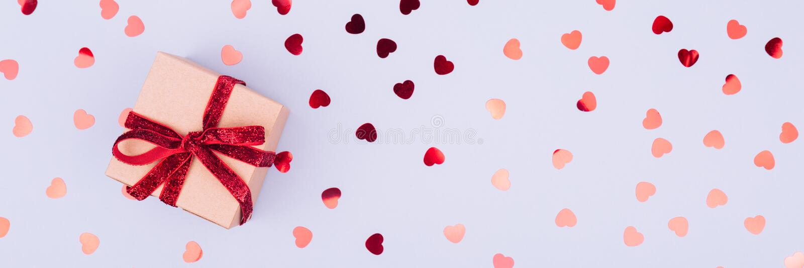 Craft box with red ribbon bow and glitter heart confetti. Valentine day concept. Trendy minimalistic flat lay design background royalty free stock photography