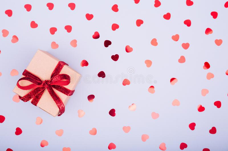 Craft box with red ribbon bow and glitter heart confetti. Valentine day concept. Trendy minimalistic flat lay design background royalty free stock image