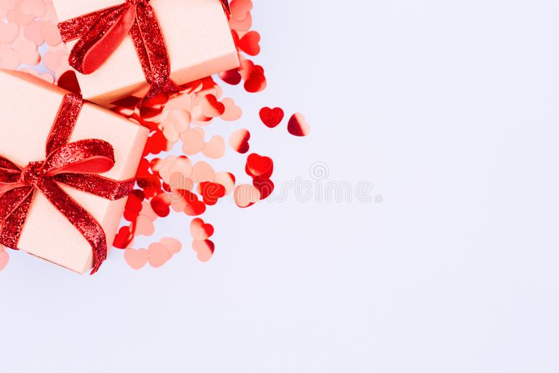 Craft boxes with red ribbon bow and glitter heart confetti. Vale royalty free stock photos