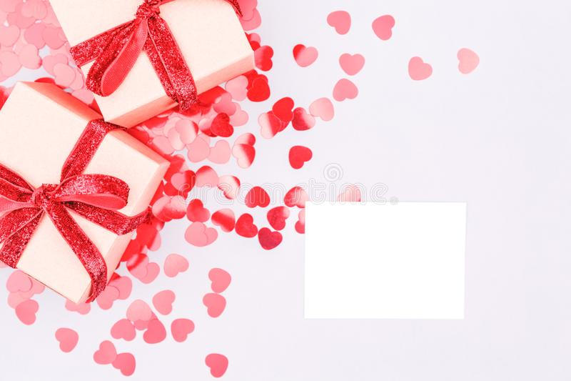 Craft boxes with red ribbon bow and glitter heart confetti. Vale royalty free stock photo