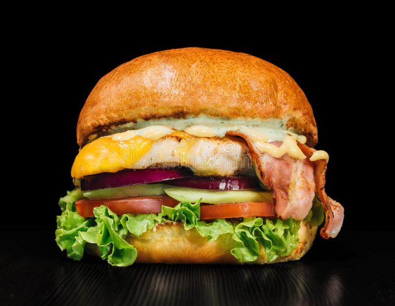 Craft burger is cooking on black background. Consist: sauce, lettuce, tomato, red onion, cucumber, cheese, bacon, air stock photography