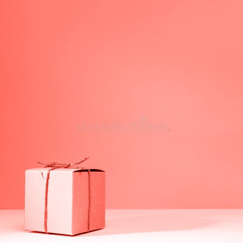 Craft cardboard gift box on the solid pink background. Holiday and gift concept . Living coral theme - color of the year 2019. Craft cardboard gift box on the royalty free stock photos
