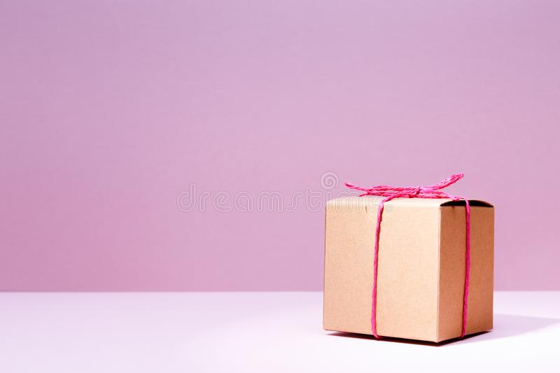 Craft cardboard gift box on the solid pink background. Holiday a stock image