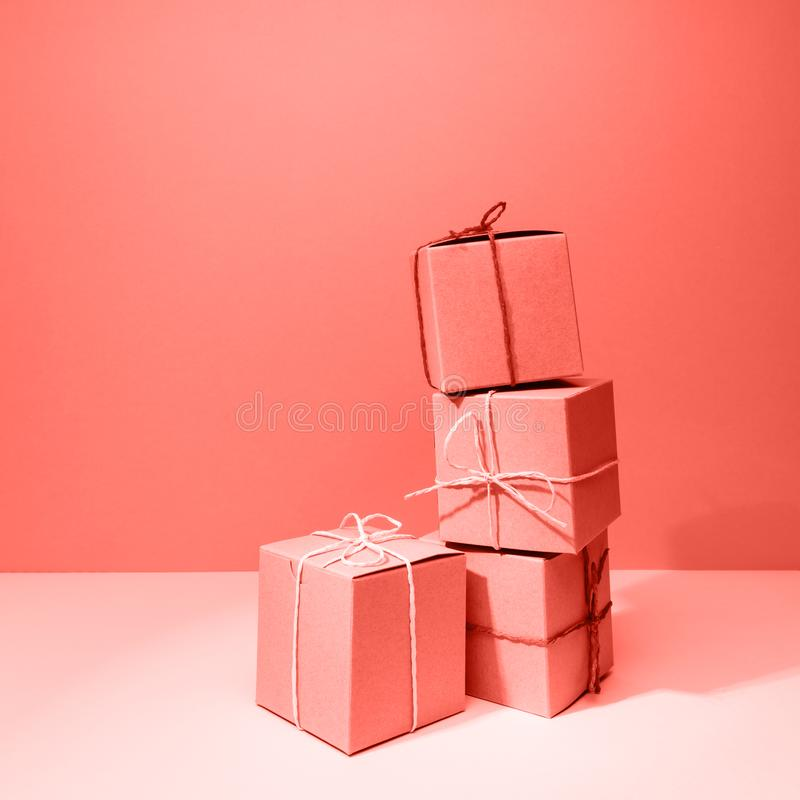 Craft cardboard gift boxes on the solid pink background. Holiday and gift concept . Living coral theme - color of the year 2019. Craft cardboard boxes on the royalty free stock images