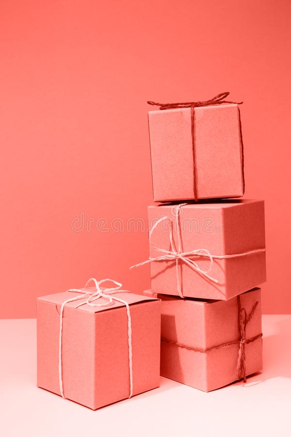 Craft cardboard gift boxes on the solid pink background. Holiday and gift concept . Living coral theme - color of the year 2019. Craft cardboard boxes on the royalty free stock photos