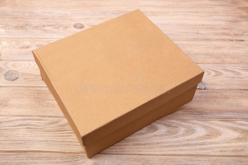 Craft cardboard package box presented on wooden table. top view.  royalty free stock photography