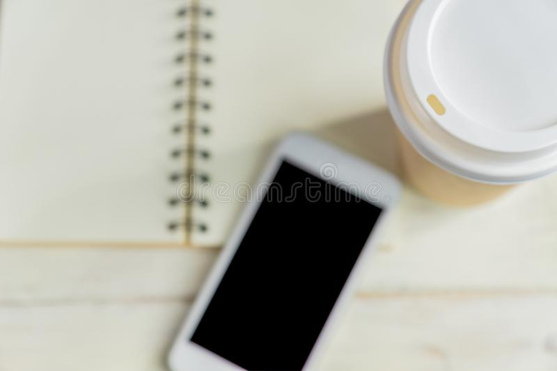 Craft disposable paper coffee cup, notebook and white smartphone on wooden background with copy space. Top view royalty free stock photography