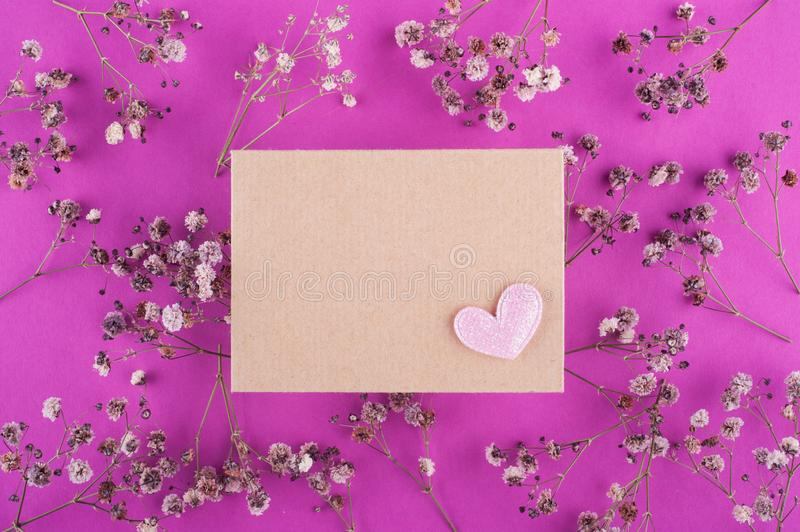 Craft envelope on pink background. And dry flowers as pattern royalty free stock images