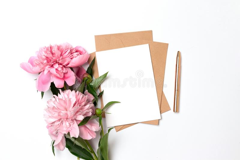 Craft envelope with a sheet of paper with a bouquet of pink peonies on a gray background. Creative mockup of craft envelope with a sheet of paper with a bouquet stock photos