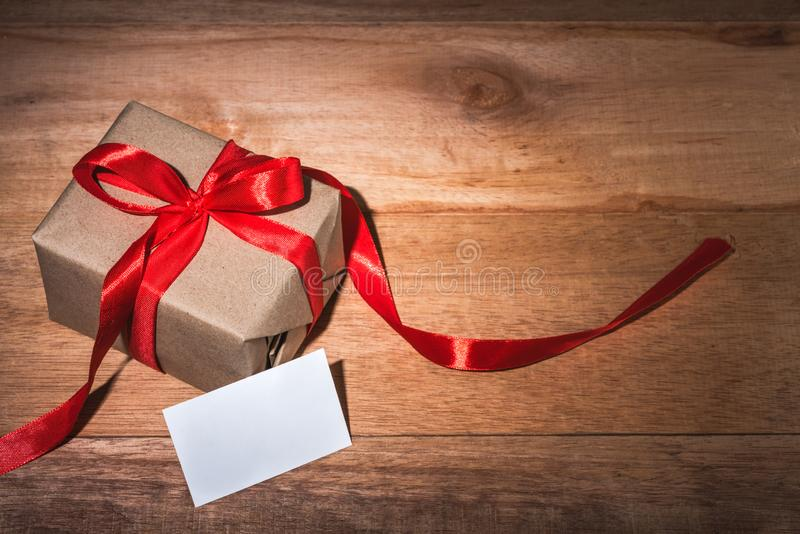 Craft gift box and white card on wooden table stock photography