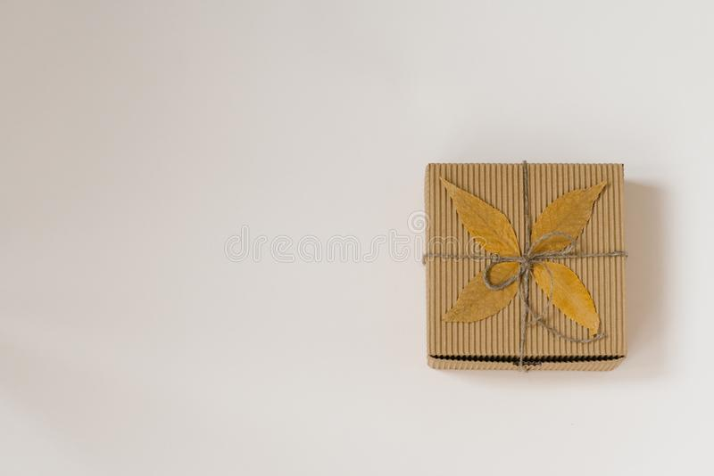 Craft gift box, tied with string with a bow and autumn fallen leaves on a beige background. Birthday gift for people born in autum stock images