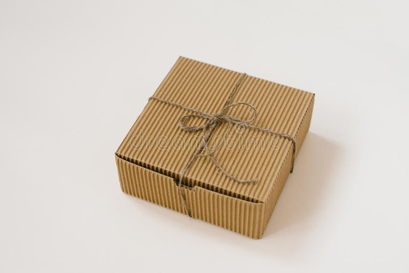 Craft gift box tied with twine with on beige background. Gift wrap for birthday royalty free stock photography