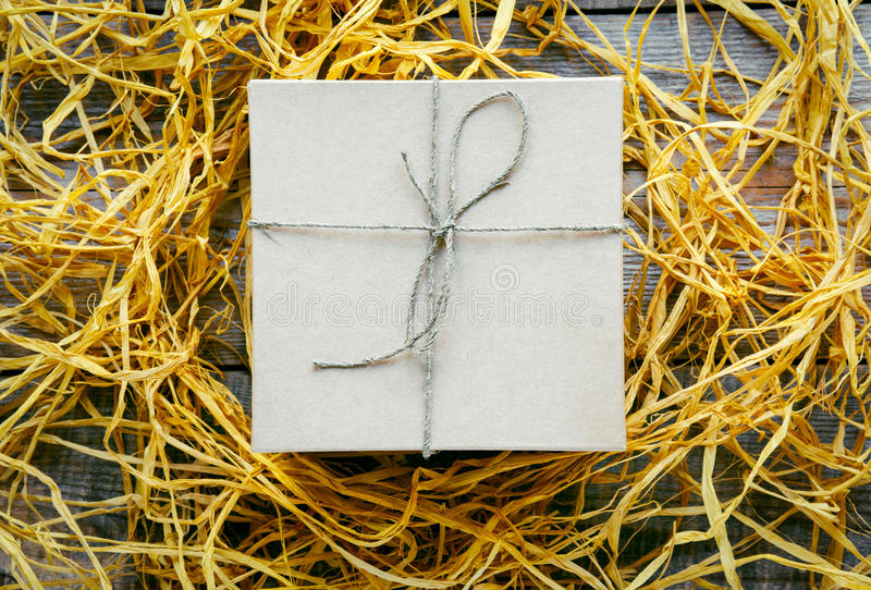 Craft gift box on wooden table with raffia or twine. Craft gift box on wooden table with natural raffia or twine close up royalty free stock images