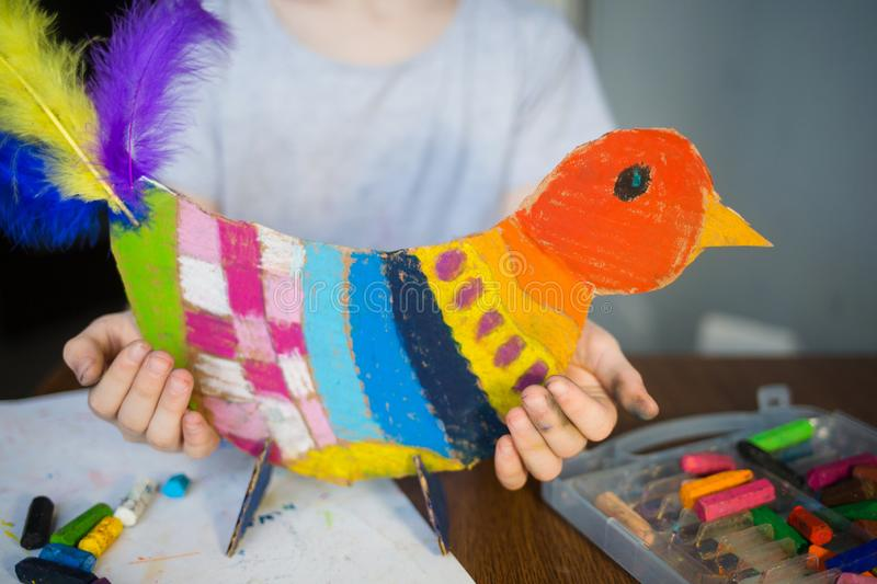 Craft with kids. bright bird, cut from cardboard and painted with wax crayons,in the hands of a child stock photography