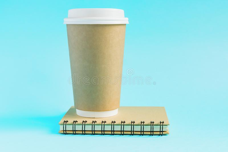 Craft paper coffee cup and notebook diary with copy space on blue background in minimalism style royalty free stock photography