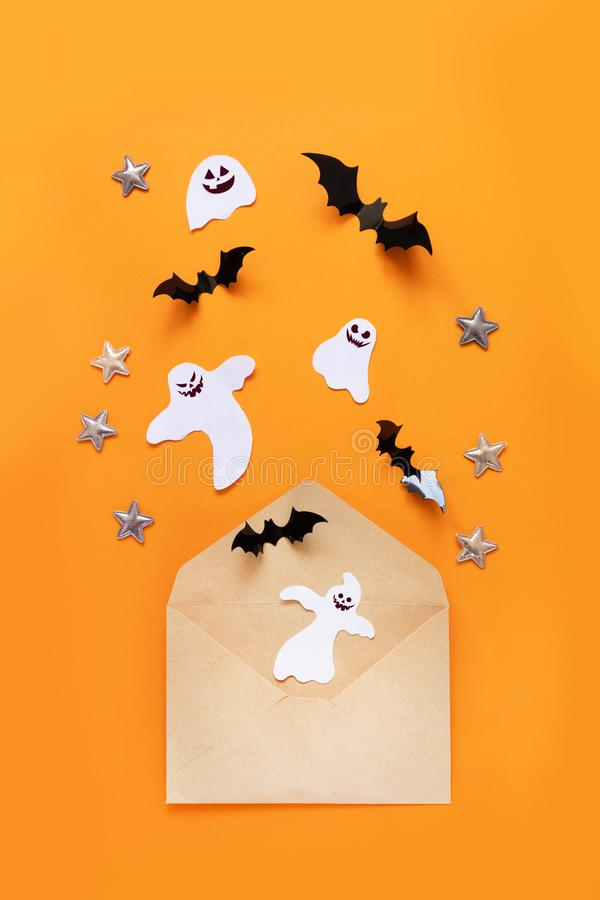 Craft paper envelope and black paper bats fly up on an orange background, top view stock photo