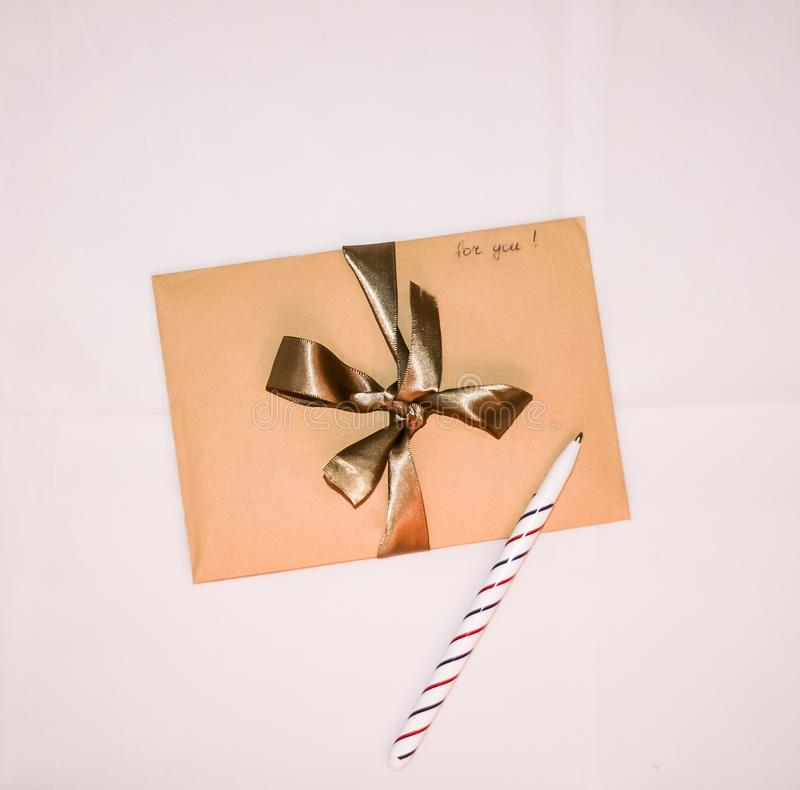 Craft paper envelope with golden ribbon, handwritten sign `for you`, and a pen. Craft paper envelope with golden ribbon and handwritten sign `for you`, and a pen royalty free stock image