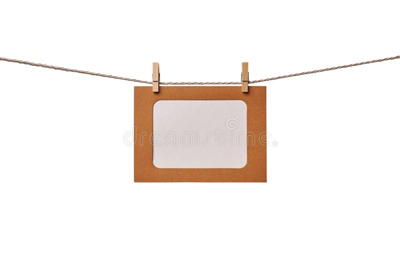 Craft paper photo frame hanging on the rope isolated on white background stock photos