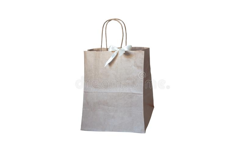 Gift paper bag with white bow isolated in grey wood backgraund. Craft paper shopping bag. Gift paper bag with white bow isolated in grey wood backgraund royalty free stock photo