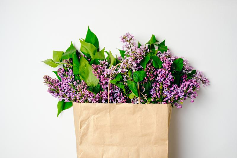 Craft paper shopping bag with lilac purple flower over white background. Creative flat lay composition, top view, overhead. Spring royalty free stock images