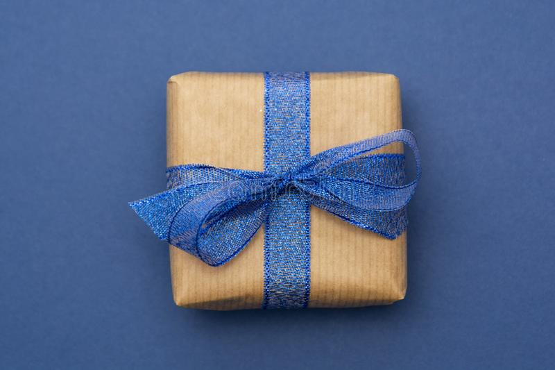 Craft paper wrapped gift box isolated on blue background, flat lay. Abstract Christmas gift stock photo