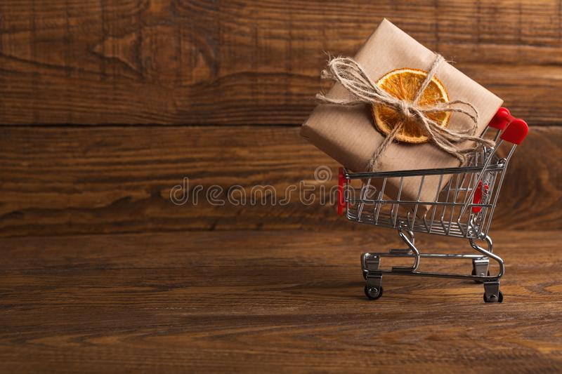Craft parcel decorated with dried orange in shopping cart royalty free stock photo