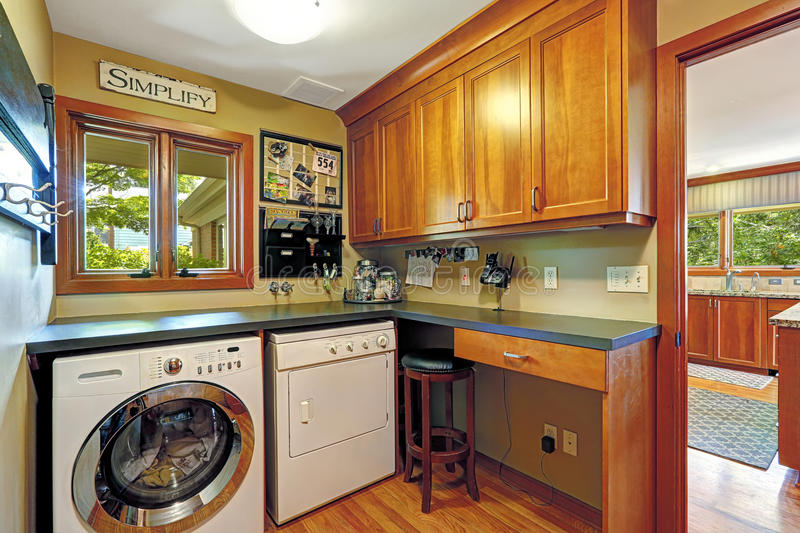 Craft room with laundry area. Small craft room with wooden storage combintaion and laundry appliances stock image