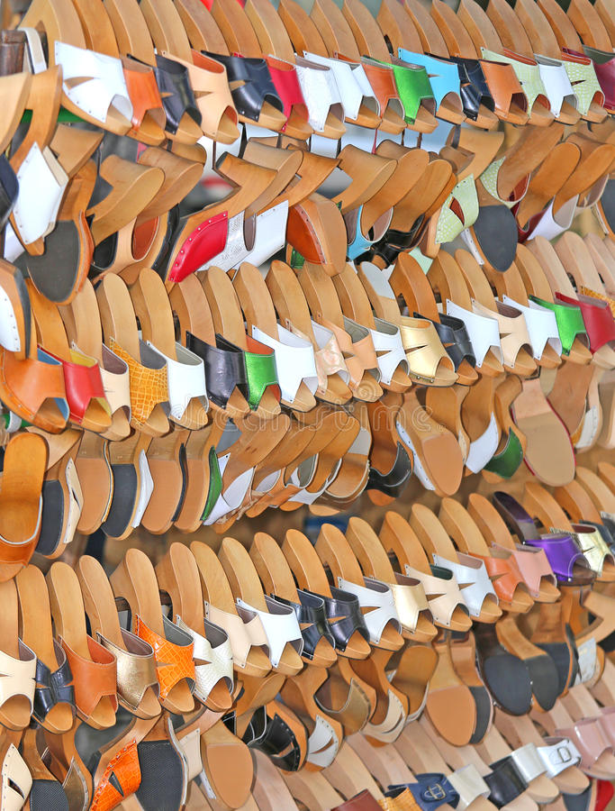 Craft store with many wooden shoes and colored leather. Hanging from the stand stock image